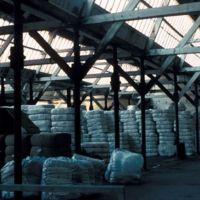 Intérieur d'un bâtiment à toit en shed (charpente bois, piliers métal), balles de laine