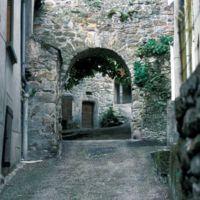 Façades dans le village : porte du village et porte de maison, plan large